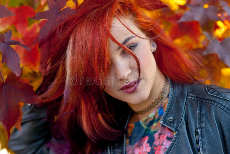 Beautiful redhead girl in autumn scene royalty free stock photography
