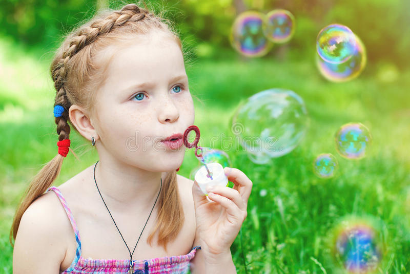 Beautiful redhead Girl blowing Soap Bubbles stock images