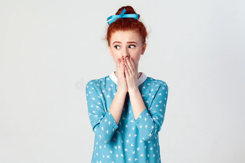 Beautiful redhead girl in blue dress doesn`t want to spread rumors or some confidential information. royalty free stock photography