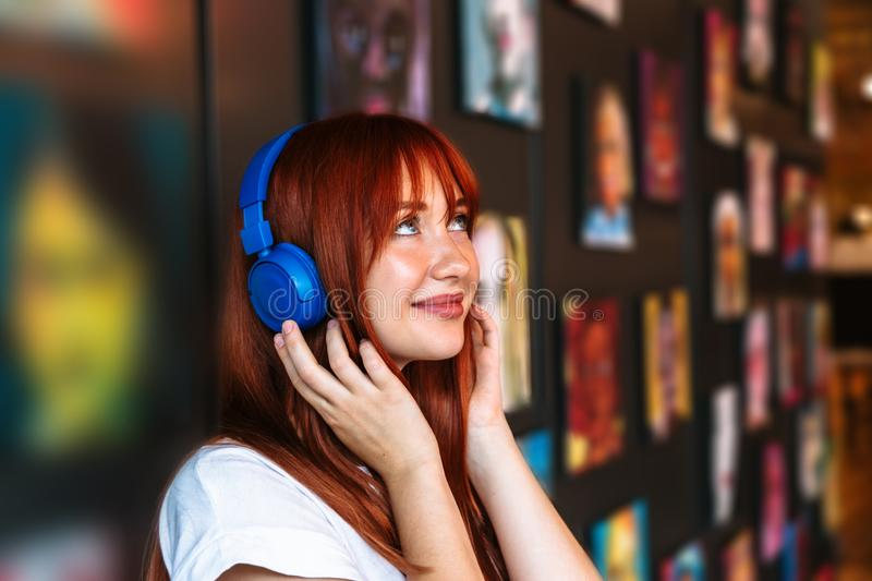 Girl in headphones stands near wall with paintings stock photos