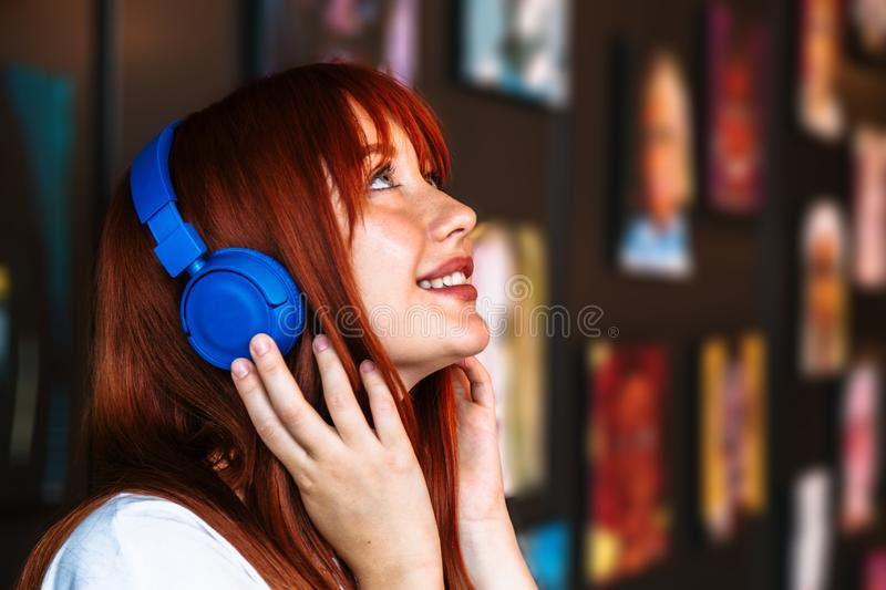 Girl in headphones stands near wall with paintings stock image