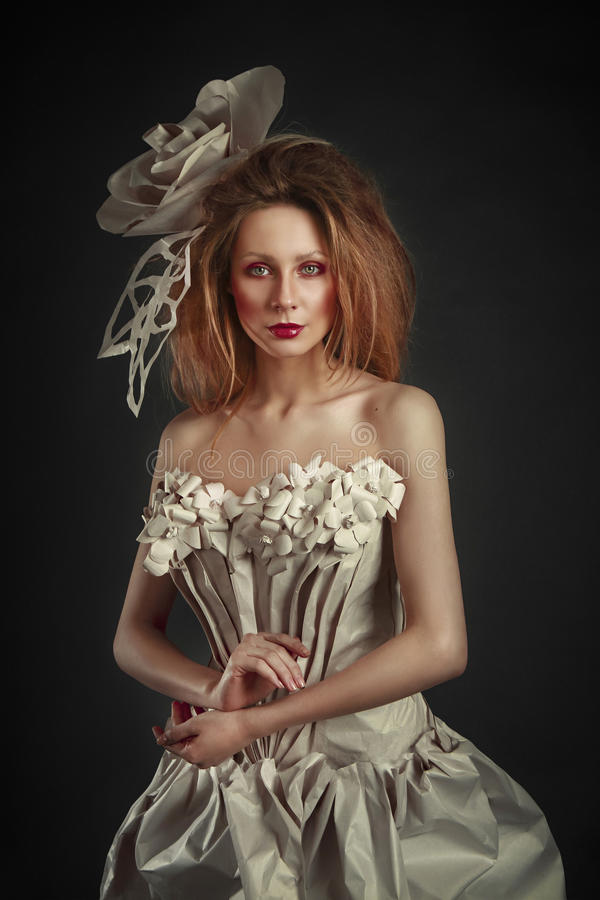 Beautiful redhead girl in elegant paper dress. Sensual image with bright makeup. Beauty model.  stock images
