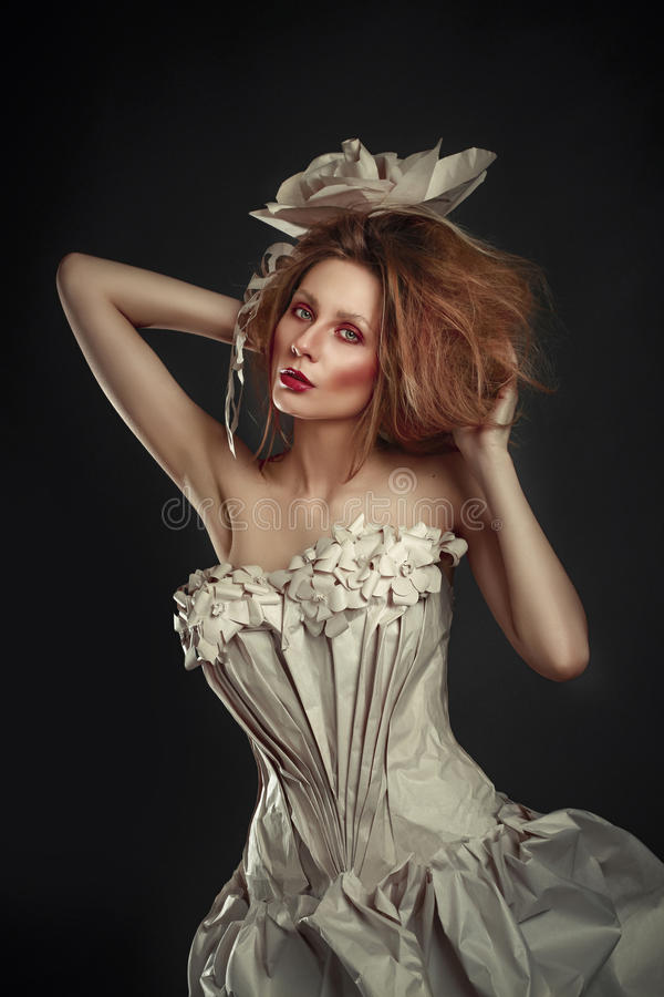 Beautiful redhead girl in elegant paper dress. Sensual image with bright makeup. Beauty model.  stock photography
