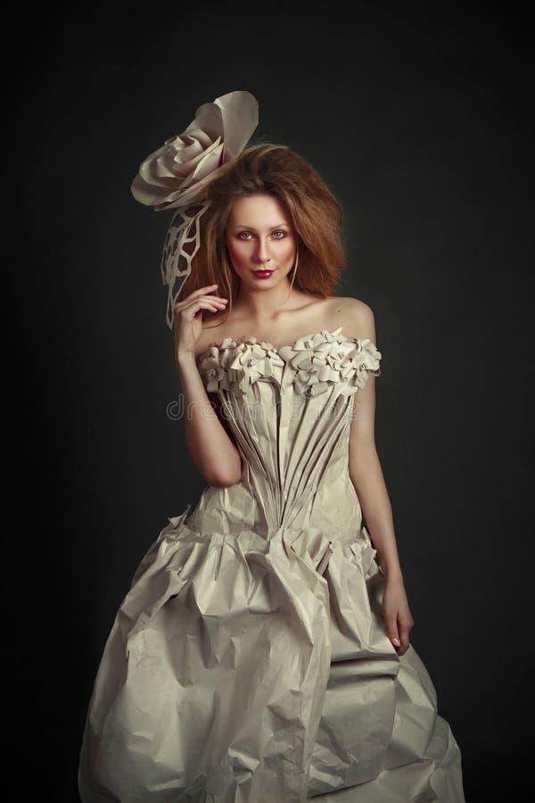 Beautiful redhead girl in elegant paper dress. Sensual image with bright makeup. Beauty model.  stock image