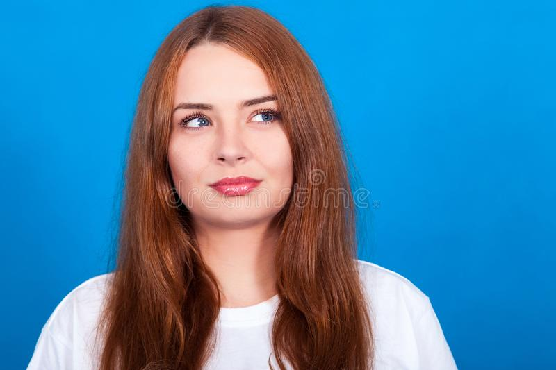 Beautiful redhead girl with freckles on a blue background thinks, sly look royalty free stock photo