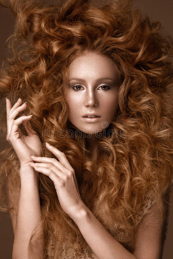 Beautiful Redhead girl with a perfectly creative curls hair and classic make-up. Beauty face. royalty free stock image