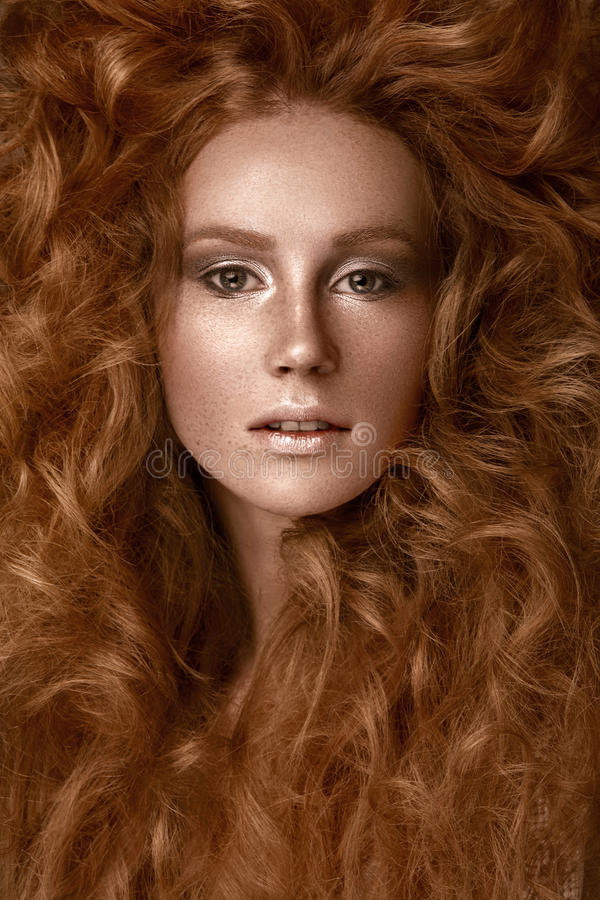 Beautiful Redhead girl with a perfectly creative curls hair and classic make-up. Beauty face. stock image