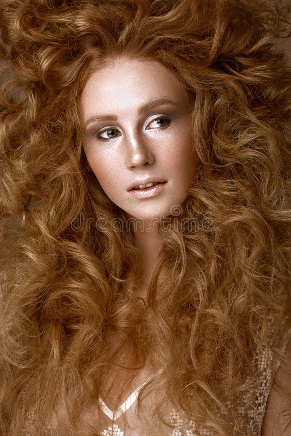 Beautiful Redhead girl with a perfectly creative curls hair and classic make-up. Beauty face. stock photo