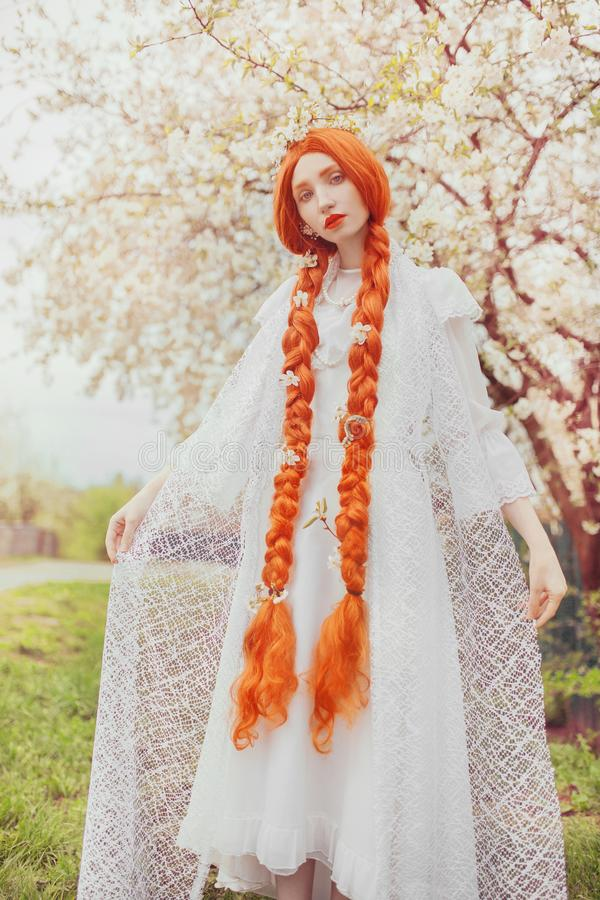 Beautiful redhead girl with plait on spring blossom plant background. Asian woman in white dress in garden. Blooming spring cherry stock image