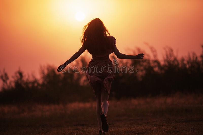 Beautiful redhead girl silhouette in a pink dress against a background dawn. Girl run towards sunrise. Misty morning dawn over the stock images