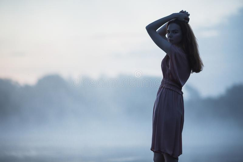 Beautiful redhead girl silhouette in a pink dress against a background dawn. Girl run towards sunrise. Misty morning dawn over the stock photos