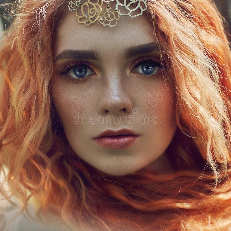 Beautiful redhead Norwegian girl with big eyes and freckles on face in the forest. Portrait of redhead woman closeup in nature stock images