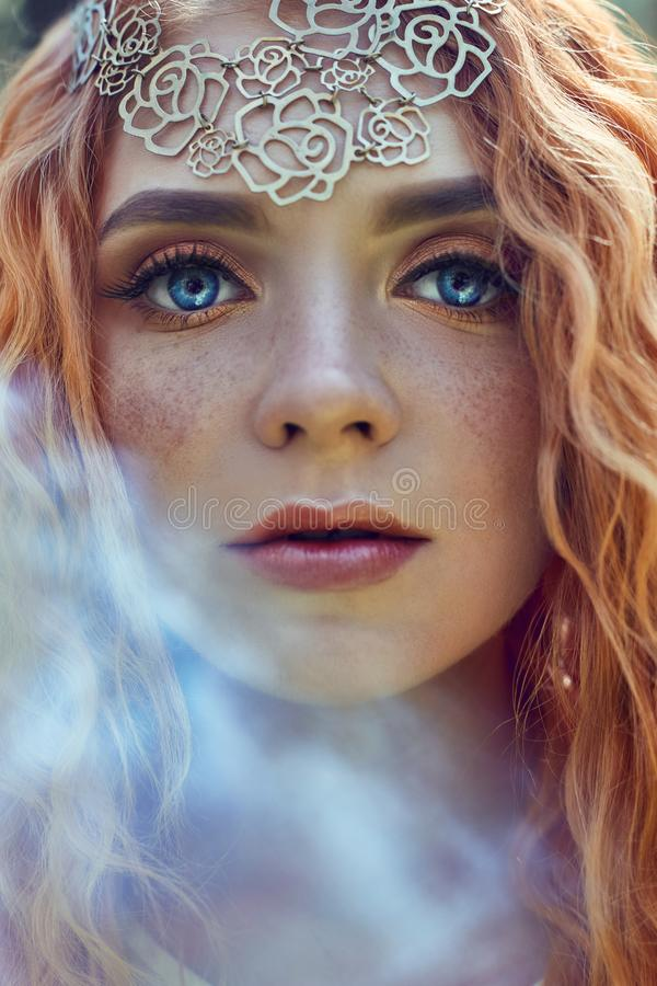 Beautiful redhead Norwegian girl with big eyes and freckles on face in the forest. Portrait of redhead woman closeup in nature stock photo