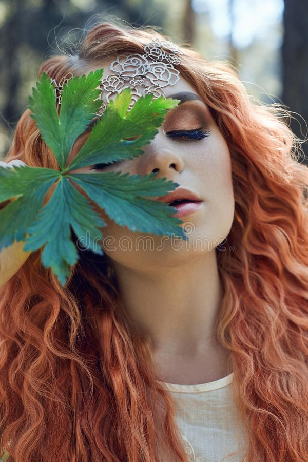 Beautiful redhead Norwegian girl with big eyes and freckles on face in the forest. Portrait of redhead woman closeup in nature royalty free stock image