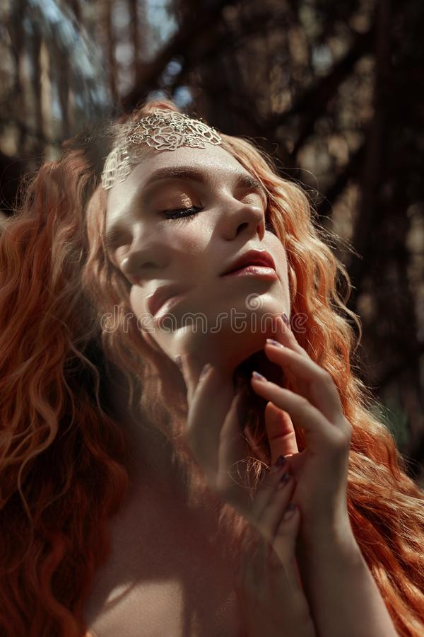 Beautiful redhead Norwegian girl with big eyes and freckles on face in the forest. Portrait of redhead woman closeup in nature stock photography