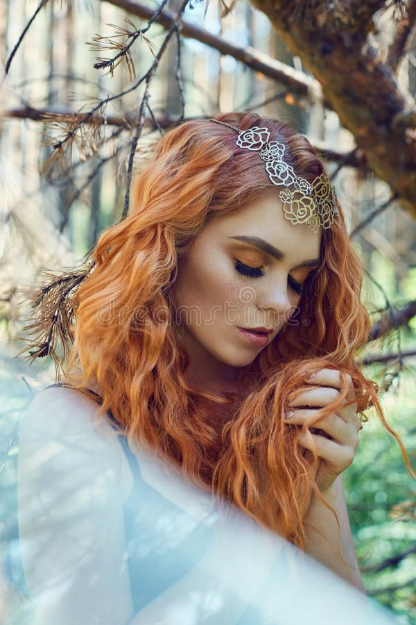 Beautiful redhead Norwegian girl with big eyes and freckles on face in the forest. Portrait of redhead woman closeup in nature royalty free stock photos