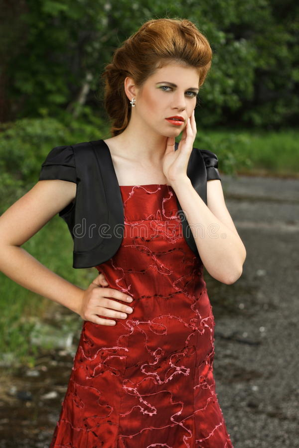 Beautiful redhead in red gown on the road in the c stock images