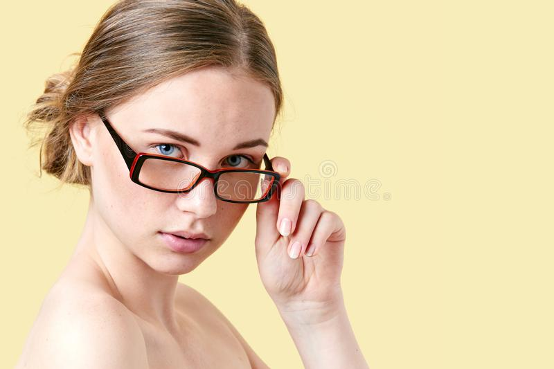 Beautiful redhead teenage girl with freckles wearing reading glasses. Young woman with glasses. royalty free stock image