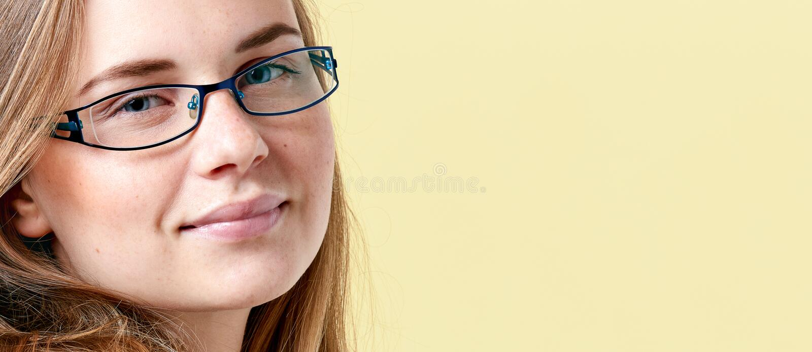 Beautiful redhead teenager girl with freckles wearing reading glasses, smiling teen portrait royalty free stock photos