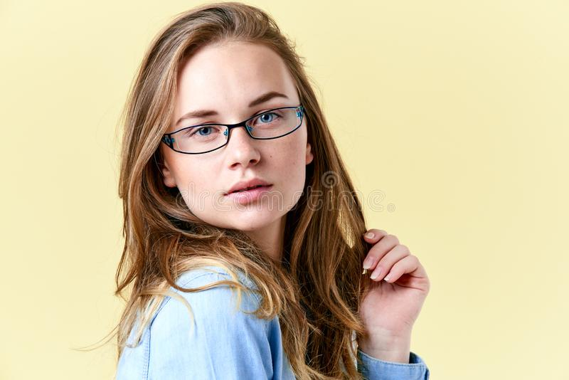 Beautiful redhead teenager girl with freckles wearing reading glasses, smiling teen portrait royalty free stock image