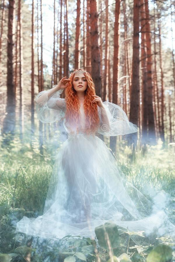 Beautiful redhead woman forest nymph in a blue transparent light dress in the woods spinning in dance. Red hair girls. Art fashion stock photography