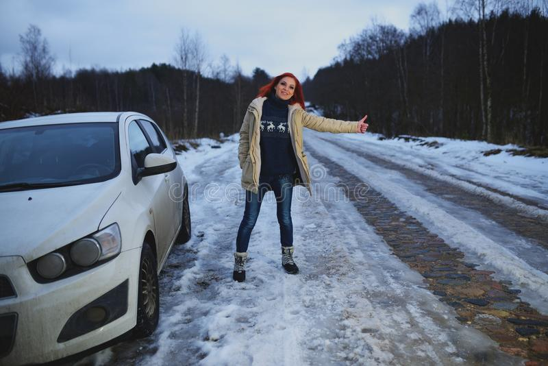 Beautiful redhead woman hitchhiking by broken car.  royalty free stock image