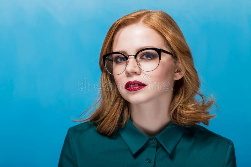 Beautiful redhead woman looking at camera. Portrait of a young girl on a blue background. stock photo