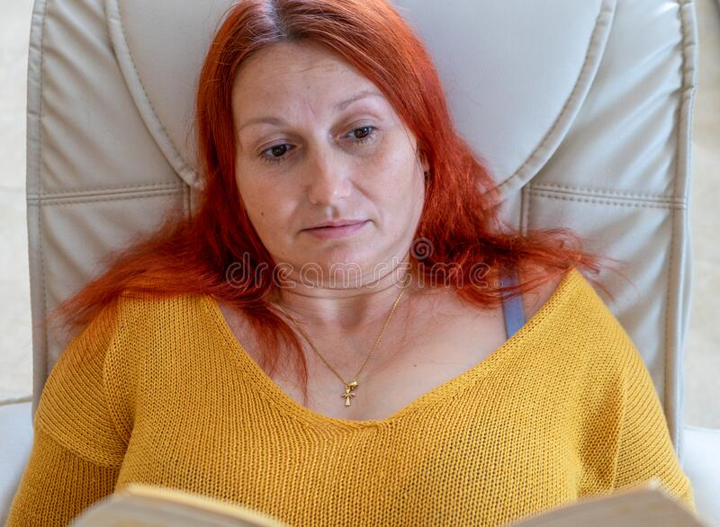 Beautiful redhead woman in yellow sweater reading a book relaxed in her living room. Entertainment concept stock photos