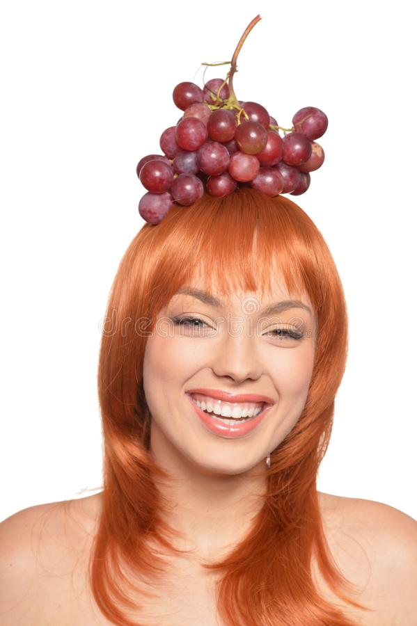Beautiful redhead young woman with red grapes on head isolated on white background. Portrait of beautiful redhead young woman with red grapes on head isolated on royalty free stock image