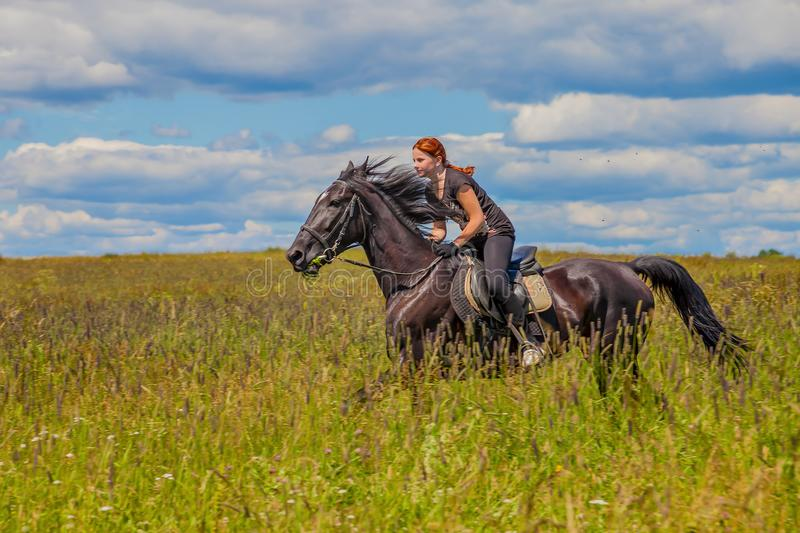 Beautiful redheaded girl riding a horse in countryside. Teen girl rides on the field with grass on a Sunny summer day royalty free stock photos