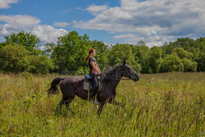 Beautiful redheaded girl riding a horse in countryside. Teen girl rides on the field with grass on a Sunny summer day stock image