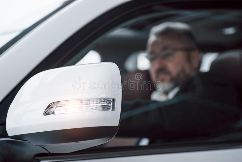Beautiful reflection from glass of vehicle mirror. Side view of senior businessman in official clothes driving a modern. New car stock photography
