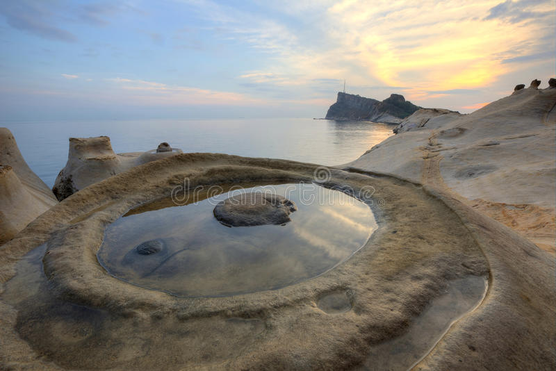 Beautiful reflection of rosy sunrise sky at Yehliu Coast Geologic Park with candlestick rock formations stock photography