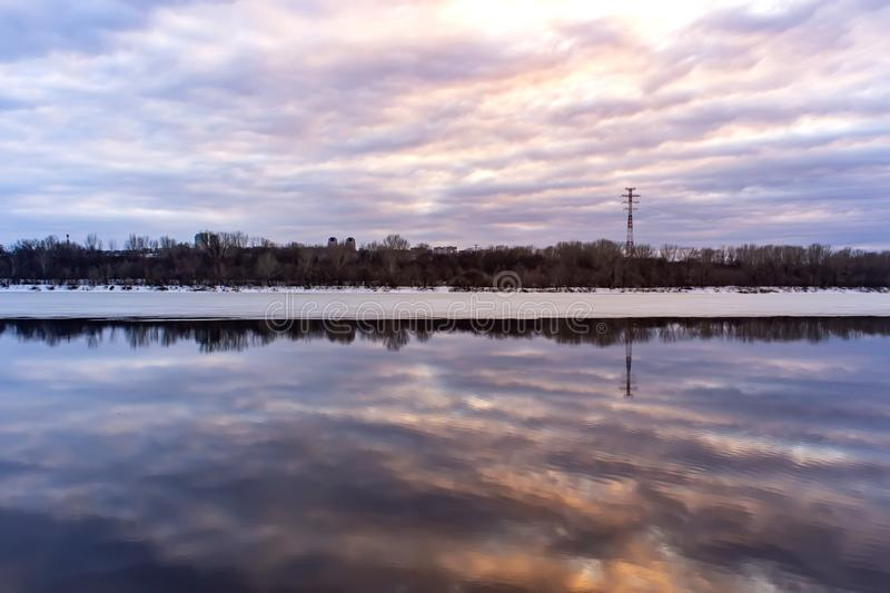 Beautiful reflection of the sky at sunset in the water on the river. Spring background. royalty free stock images