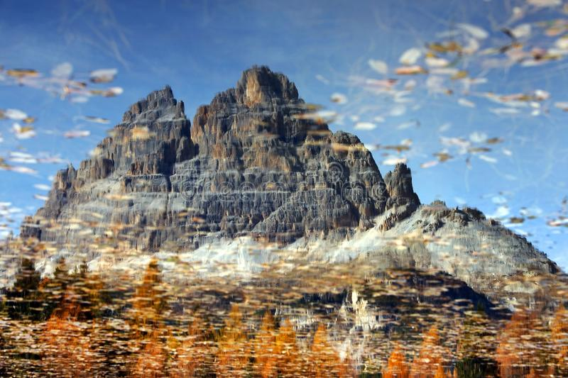 Beautiful reflection of Tre Cime di Lavaredo and the colorful forest in Antorno lake at sunset in autumn. royalty free stock images