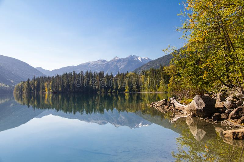 Beautiful reflections of forested Birkenhead lake shoreline and mountains. Mirror-like reflections of forested Birkenhead lake shoreline and mountains in Fall stock image