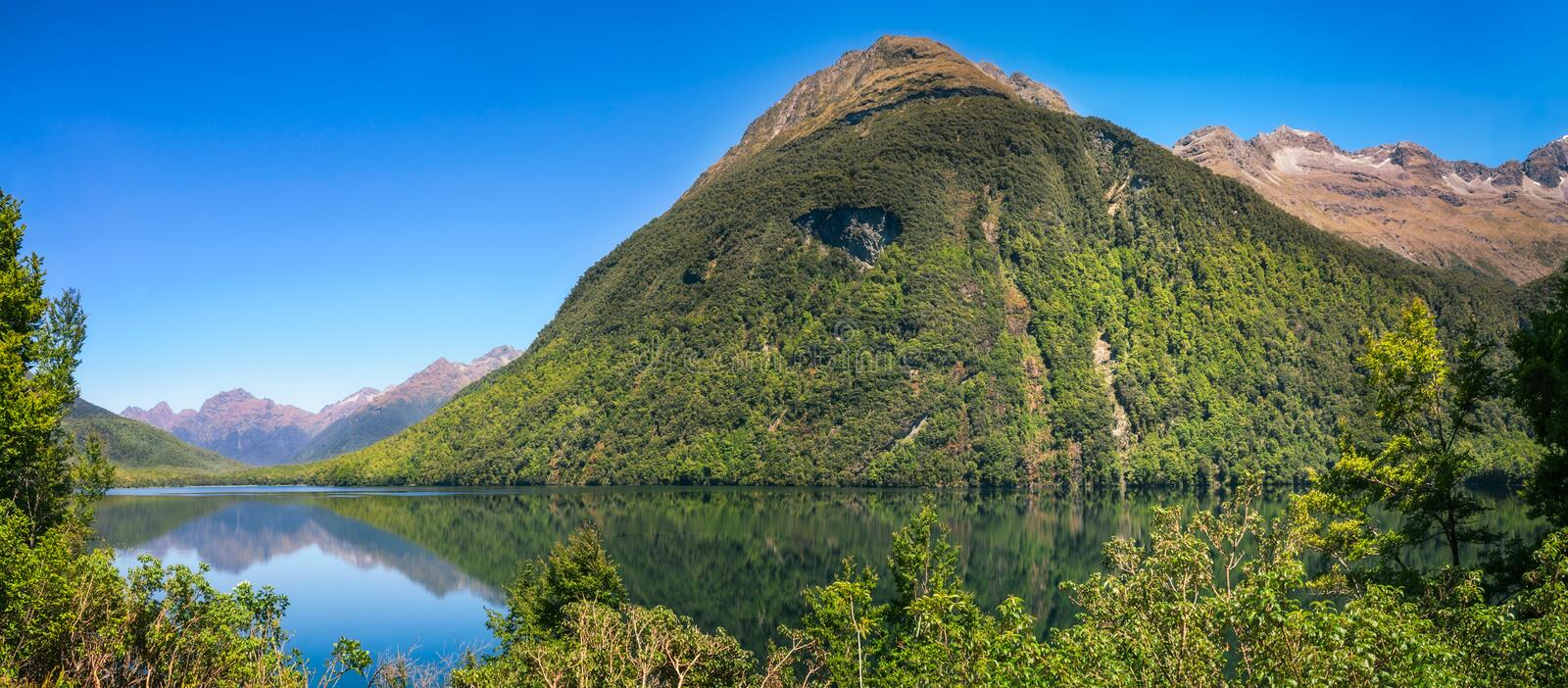 Beautiful reflections at Lake Gunn, New Zealand. Beautiful reflections at Lake Gunn on the way to Milford Sound in Fiordland National Park, New Zealand, South royalty free stock image