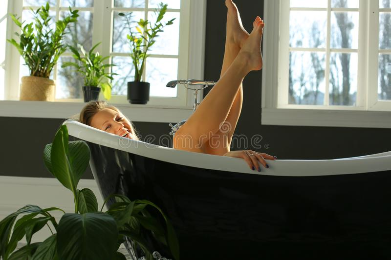 Happy pretty woman is relaxing in bath royalty free stock images