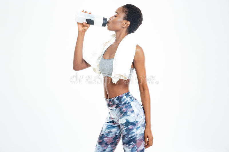 Beautiful relaxed young african american sportswoman standing and drinking water royalty free stock photos