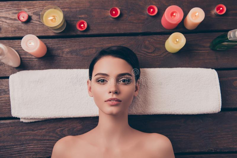 Beautiful relaxed young woman laying in spa salon on towel on wooden background copy space red candles charming face. Bea stock photography