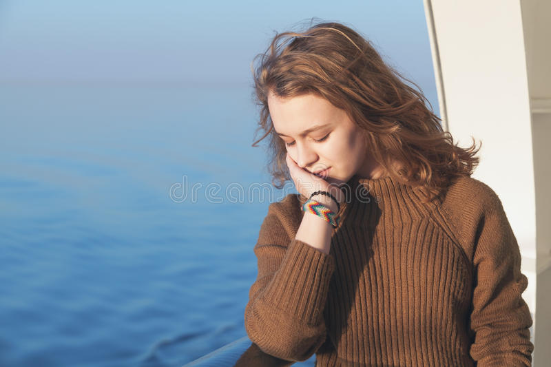 Beautiful relaxing blond teenage girl portrait. Beautiful relaxing blond teenage girl stands on the walking deck of cruise ship, close-up outdoor portrait stock image