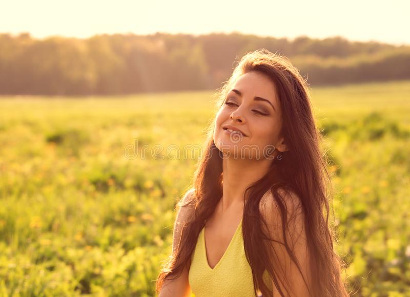 Beautiful relaxing woman with closed eyes is deep breathing and meditating with long amazing hair on nature bright sunset summer stock photo