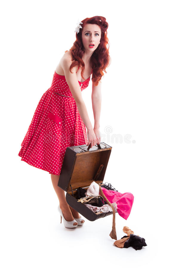 Beautiful retro pin-up girl with red polka dot dress. And suitcase with clothes falling out stock photos