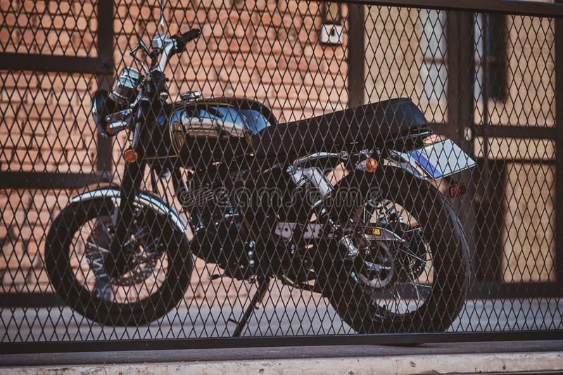 Beautiful retro vintage motorbike near brick wall. Brand new, shiny black retro chopper is parked next to brick building, behind the fence royalty free stock photos