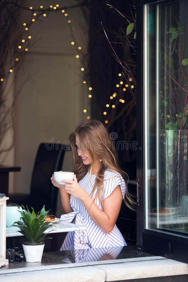 Beautiful rich casual blonde stylish fashion business woman at the cafe table drinking coffee and smiling stock images