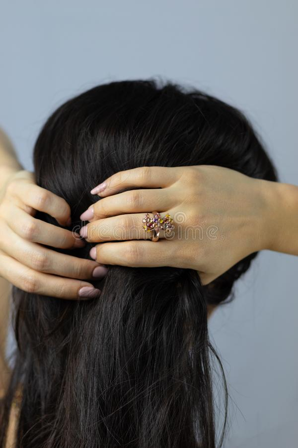 Beautiful ring of colored stones and gold on the finger of a woman touching her hair stock photos