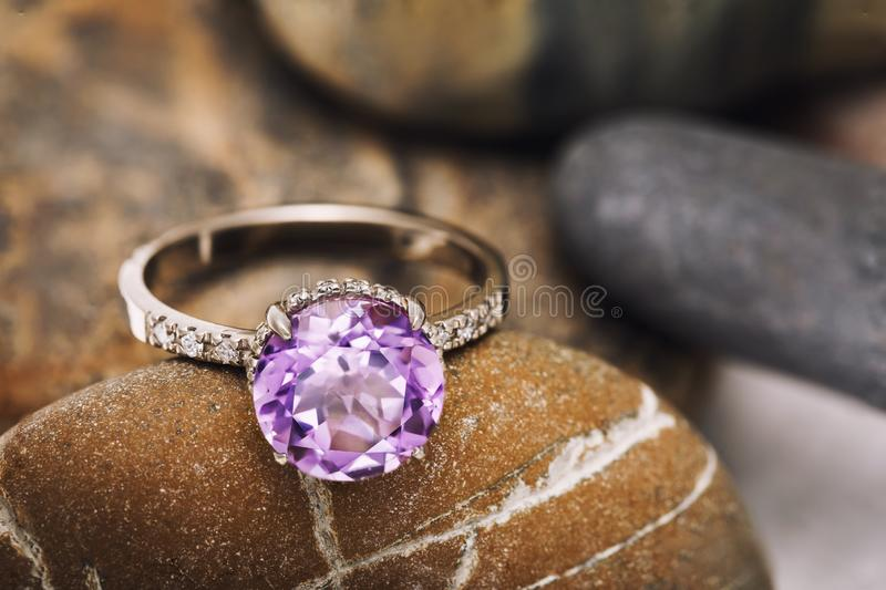 Beautiful ring on stones from white gold with amethyst and small diamonds. Gemstone closeup stock photo