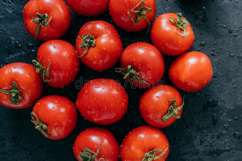 Beautiful ripe fresh red tomatoes growned in greenhouse. Water drops on heirloom vegetables isolated on dark background. royalty free stock photos