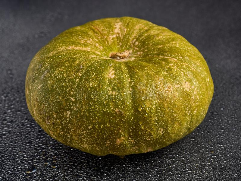 Beautiful ripe pumpkin lying on black wet glass and falling water drops royalty free stock photos