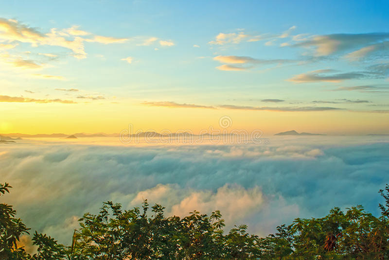 Beautiful rising sun in the early morning over sea of fog on hill of Phu Tok. stock photos